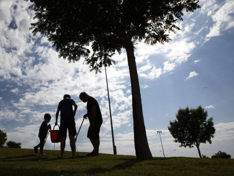 Calvin Muraco of Las Vegas, 4, left, picks up trash with his sister Ainslee, 10, center and his ...