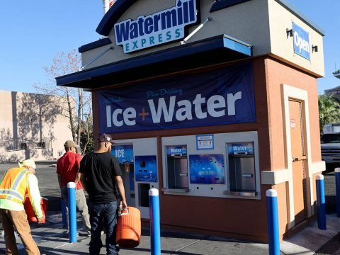 Workers line up for ice at a kiosk on the corner of Smoke Ranch Road and Jones Boulevard in Las ...