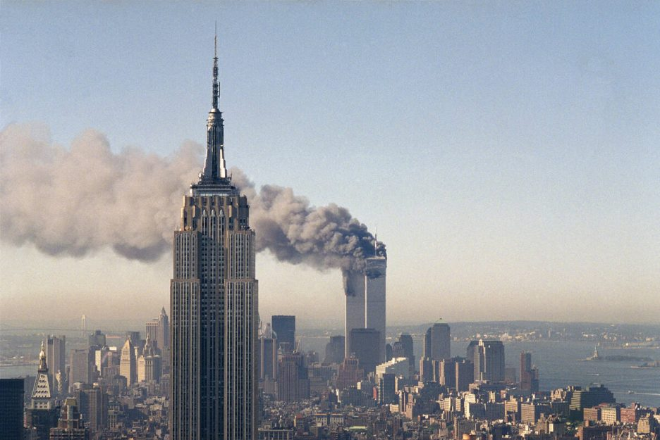 The twin towers of the World Trade Center burn behind the Empire State Building in New York on ...