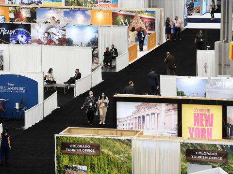 Vendors move around the show floor on the the opening day of the U.S. Travel Association's IPW ...