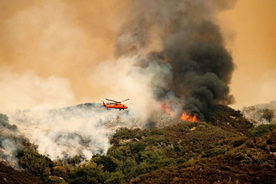 A helicopter prepares to drop water on the KNP Complex Fire in Sequoia National Park, Calif., o ...