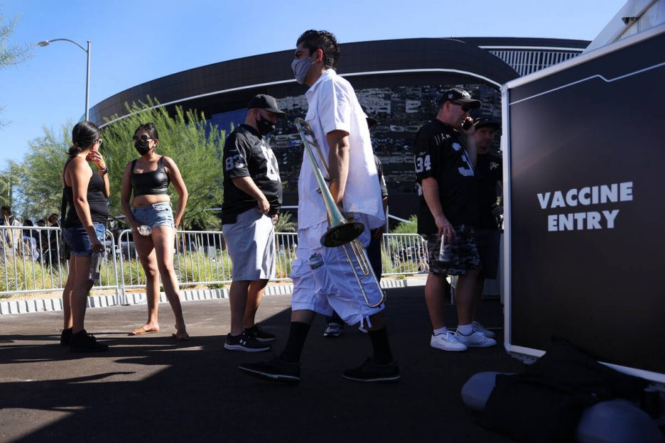 People line up to get the COVID-19 vaccine before the start of an NFL football game between the ...