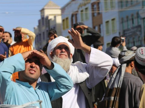 People look up at a dead body hanged by the Taliban from a crane in the main square of Herat ci ...