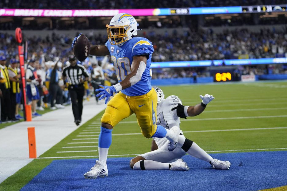 Los Angeles Chargers running back Austin Ekeler scores a touchdown as Las Vegas Raiders outside ...