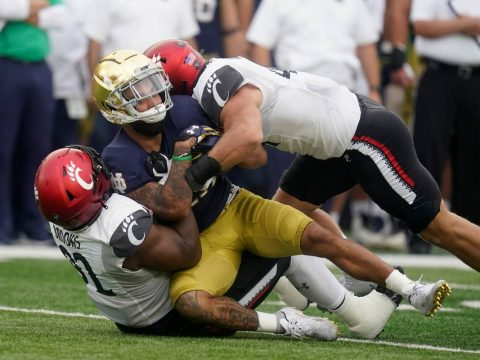 Notre Dame's Kyren Williams (23) is tackled by Cincinnati's Curtis Brooks (92) and Joel Dublank ...