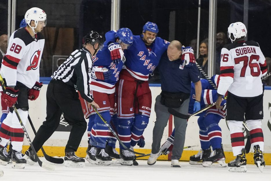 New York Rangers' Ryan Reaves is helped off the ice during the first period of the team's NHL p ...