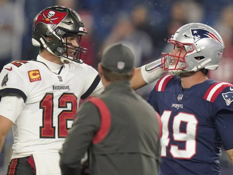 Tampa Bay Buccaneers quarterback Tom Brady (12) meets with New England Patriots long snapper Jo ...