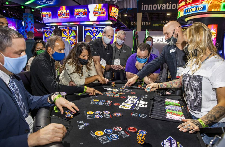 Gabe Baron and Kari Walker with AGS explain the features of the Jackpot Hold'Em table game duri ...