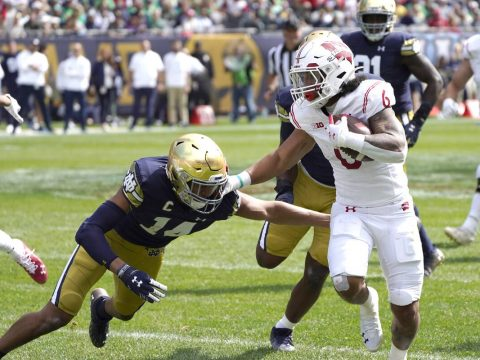 Wisconsin running back Chez Mellusi carries the ball as Notre Dame safety Kyle Hamilton comes u ...