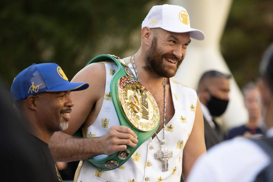 WBC heavyweight champion Tyson Fury poses for photos with trainer Sugar Hill after a press conf ...